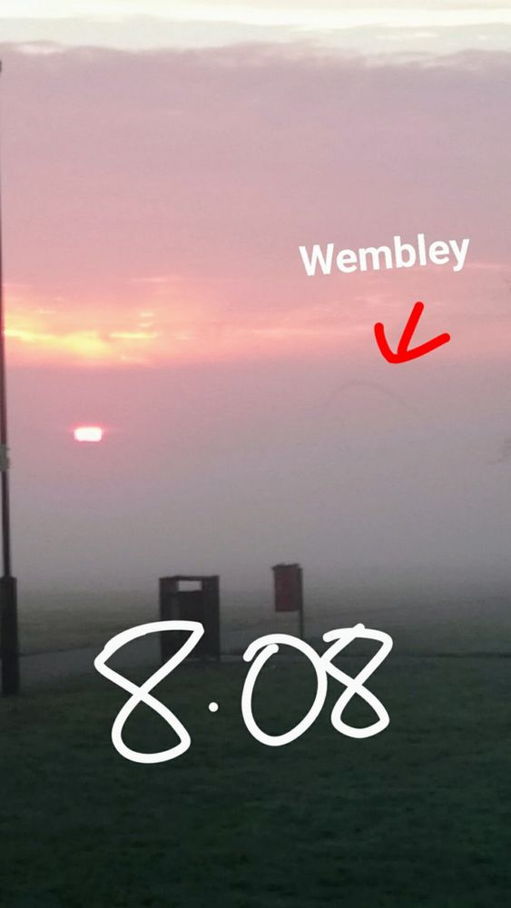 8:08 am, Wembley Stadium through heavy mist with the sunrise in view.
